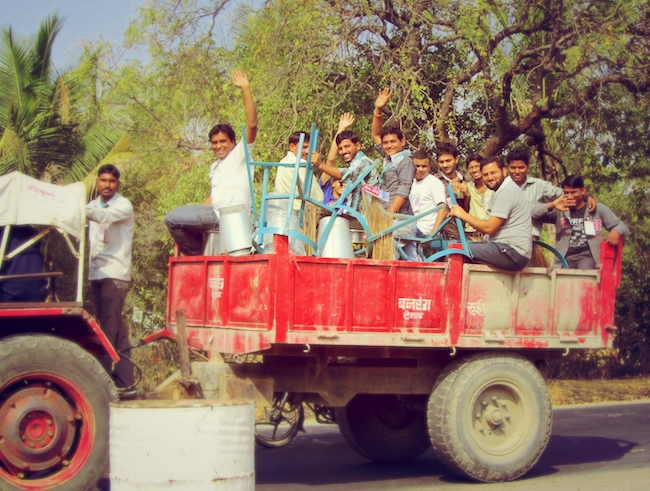 A truck containing joyful Indian men.