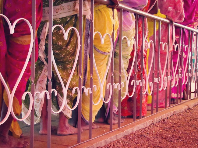 A metal heart fence and colorful saris.