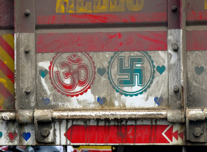 Om and Swastika symbolism on a truck in India. Photo by Thessilian