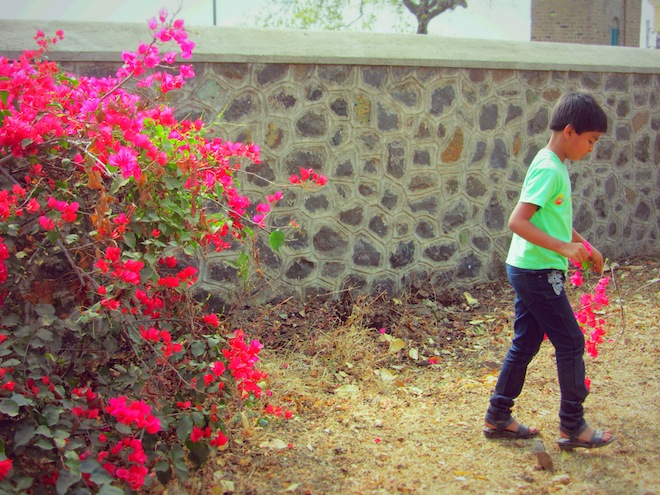 An Indian kid walks off with pretty flowers.